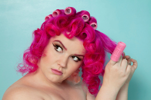 Young woman removing hair curlers over colored backgroundの写真素材 [FYI03650861]