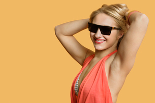 Portrait of a young woman wearing sunglasses with hands in hair over colored backgroundの写真素材 [FYI03650894]