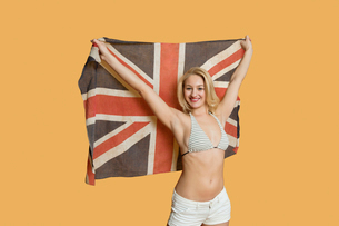 Portrait of a beautiful young woman holding British flag with arms raised over colored backgroundの写真素材 [FYI03650901]