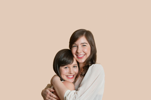 Portrait of young female friends hugging over colored backgroundの写真素材 [FYI03650912]