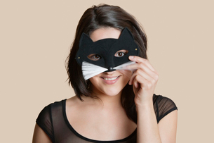 Portrait of a young woman looking through eye mask over colored backgroundの写真素材 [FYI03650913]