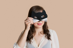Young woman looking through eye mask over colored backgroundの写真素材 [FYI03650915]