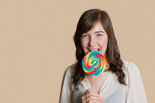 Portrait of a beautiful young woman with lollipop over colored backgroundの写真素材 [FYI03650919]