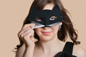 Portrait of a young woman looking through eye mask over colored backgroundの写真素材 [FYI03650931]