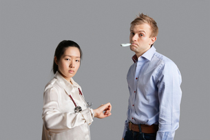 Portrait of a patient with thermometer in mouth standing with doctorの写真素材 [FYI03650944]