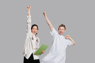 Portrait of doctor and patient cheering up with raised armsの写真素材 [FYI03650951]