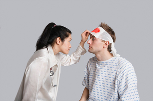 Young female doctor examining an injured male patientの写真素材 [FYI03650955]