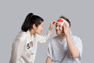 Patient suffering from pain while doctor examining himの写真素材 [FYI03650956]