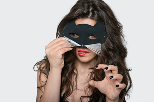 Portrait of sensuous young woman wearing cat mask while biting lip over gray backgroundの写真素材 [FYI03650976]