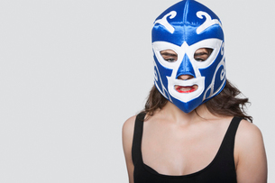 Portrait of a young woman wearing wrestling mask over gray backgroundの写真素材 [FYI03650979]