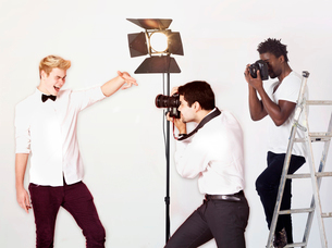 Paparazzi taking photographs of male actor over white backgroundの写真素材 [FYI03650981]