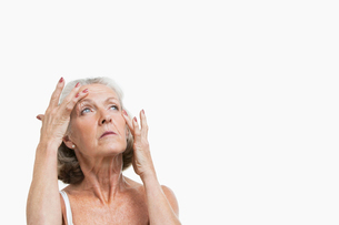 Senior woman suffering from headache against white backgroundの写真素材 [FYI03650999]