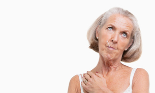 Unwell senior woman with thermometer in mouth against white backgroundの写真素材 [FYI03651009]