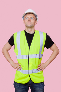 Handsome construction worker with hands on hips over pink backgroundの写真素材 [FYI03651015]