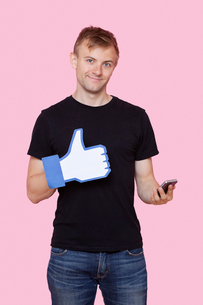Portrait of a happy young man with cell phone holding fake like button over pink backgroundの写真素材 [FYI03651018]