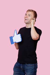 Cheerful young man using cell phone while holding fake like button over pink backgroundの写真素材 [FYI03651020]