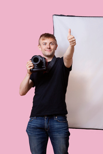 Happy photographer holding camera with thumbs up gesture over pink backgroundの写真素材 [FYI03651028]