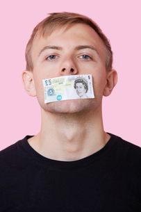 Portrait of a young man with paper money stuck over his mouth against pink backgroundの写真素材 [FYI03651031]