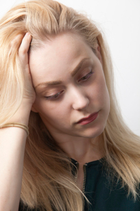 Young woman suffering from headache against white backgroundの写真素材 [FYI03651062]