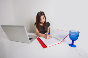 Young businesswoman writing on diary at office deskの写真素材 [FYI03651080]