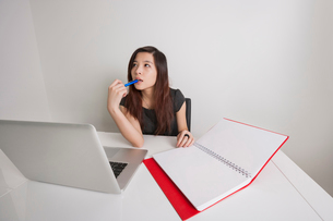 Thoughtful young businesswoman with diary and laptop at office deskの写真素材 [FYI03651081]