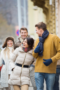 Cheerful young couples in warm clothing on city streetの写真素材 [FYI03651107]