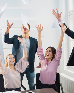 Businesspeople throwing papers in the air at officeの写真素材 [FYI03651117]