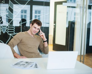 Handsome young businessman using smart phone in officeの写真素材 [FYI03651120]