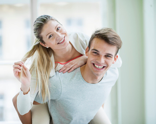 Portrait of happy young man giving piggyback ride to woman at homeの写真素材 [FYI03651126]