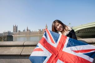 Portrait of happy woman holding British flag against Big Ben at London, England, UKの写真素材 [FYI03651146]