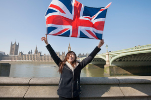 Happy woman holding British flag while standing against Big Ben at London, England, UKの写真素材 [FYI03651147]
