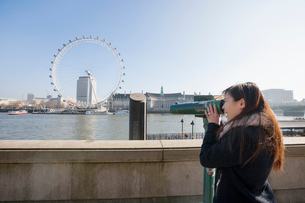 Young woman looking at London Eye through stationary viewer at London, England, UKの写真素材 [FYI03651149]