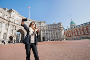 Happy woman taking self portrait against Admiralty Arch in London, England, UKの写真素材 [FYI03651153]