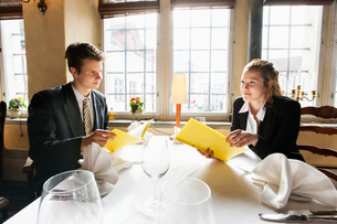Young business couple with menus at restaurant tableの写真素材 [FYI03651159]