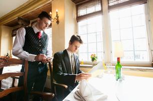Waiter taking businessman's order at restaurantの写真素材 [FYI03651160]