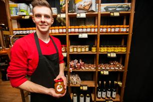 Portrait of smiling salesperson holding jar in supermarketの写真素材 [FYI03651187]