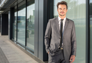 Portrait of handsome young businessman standing outside office buildingの写真素材 [FYI03651197]