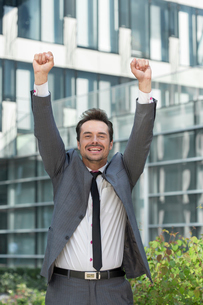Portrait of cheerful businessman celebrating success outside office buildingの写真素材 [FYI03651202]