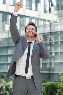 Excited young businessman using cell phone outside officeの写真素材 [FYI03651205]