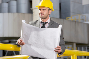 Young businessman holding blueprint while looking away at construction siteの写真素材 [FYI03651228]