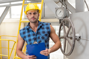 Portrait of confident male worker holding clipboard in industryの写真素材 [FYI03651230]