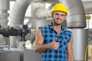 Portrait of confident young worker gesturing thumbs up in industryの写真素材 [FYI03651236]