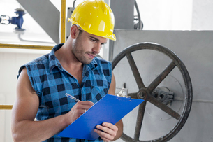 Young male worker writing on clipboard by large valve in industryの写真素材 [FYI03651247]