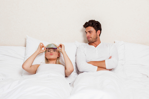 Displeased young man looking at woman wearing eye mask in bedの写真素材 [FYI03651255]