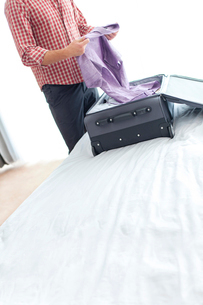 Midsection of young businessman unpacking suitcase in hotel roomの写真素材 [FYI03651265]