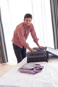 Portrait of confident young businessman unpacking suitcase on bedの写真素材 [FYI03651268]