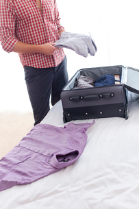Midsection of young businessman unpacking luggage in hotel roomの写真素材 [FYI03651270]