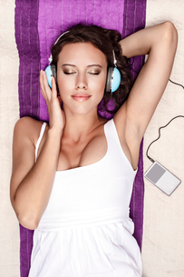 Young woman listening to music through MP3 player using headphones while lying on picnic blanketの写真素材 [FYI03651307]