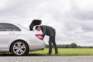 Full length side view of young businessman looking in car trunk at countrysideの写真素材 [FYI03651314]