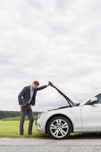 Side view of young businessman examining broken down car engine at countrysideの写真素材 [FYI03651319]
